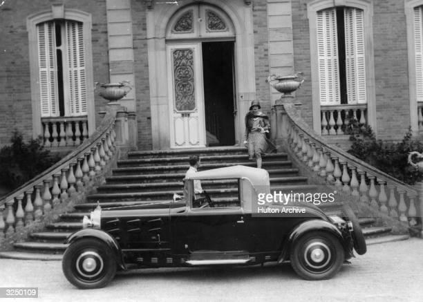 A Type 44 Bugatti with twoseater drophead coupe coachwork parked outside the Bugattiowned Chateau St Jean in Dorlisheim near Bugatti's Molsheim...