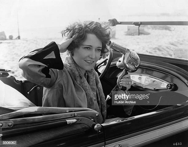 American actress Dorothy Sebastian using her hand-held hairdryer which operates from a battery on the dashboard of her car so that whenever she goes...