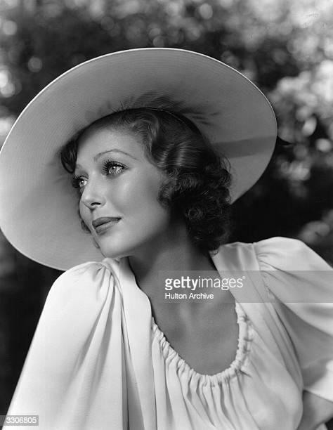 American actress Loretta Young wearing a simple scoopnecked sports dress in heavy white crepe with a large brimmed sun hat