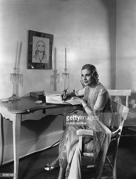 American silent screen star Lilyan Tashman sits writing in her dressing room Above her head is a framed caricature of herself