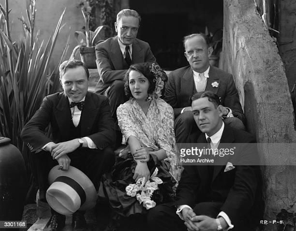 Bebe Daniels is sitting with the film executives during the production of 'Rio Rita' Left to right bottom row are Russell Mack P H Townsend and...
