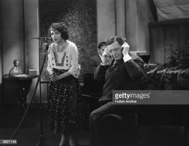 Bebe Daniels works on the musical score with Otto Morendo, her singing teacher during the filming of the film 'Rio Rita', directed by Luther Reed for...