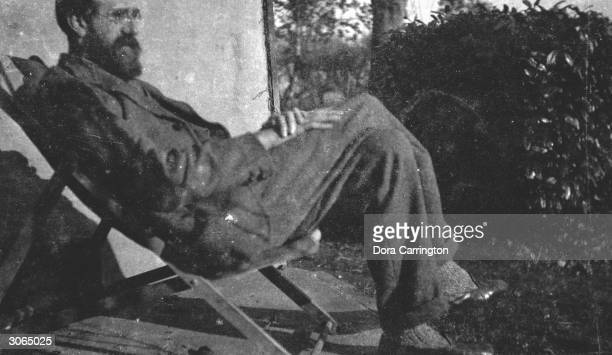 British biographer and literary critic Lytton Strachey relaxes in a deckchair at Ham Spray in Wiltshire the home he shared with painter Dora...