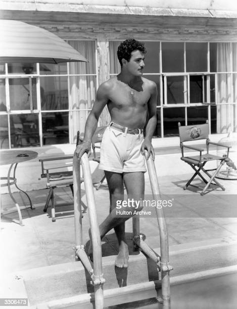 Hollywood actor Gilbert Roland poses by the steps of the swimming pool at his home He is about to star in the United Artists talkie 'New York Nights'