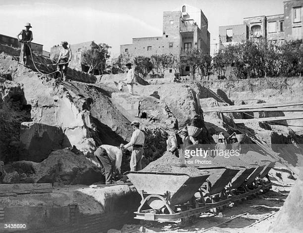 Labourers loading earth onto rail trucks during the archaeological excavation of the ancient town of Herculaneum, destroyed, along with Pompeii, in...