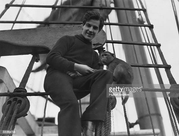 Mexican actor Ramon Novarro sitting in the rigging of a ship with a monkey during a break in the filming of 'China Bound', an MGM production.