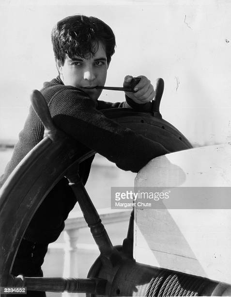Mexican heartthrob Ramon Novarro leans on a ship's wheel in a scene from the MGM film 'China Bound'