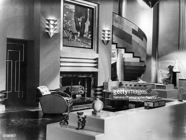 The art deco interior of a house which serves as the set for the film 'Our Modern Maidens', with a sweeping staircase leading from the lounge area....