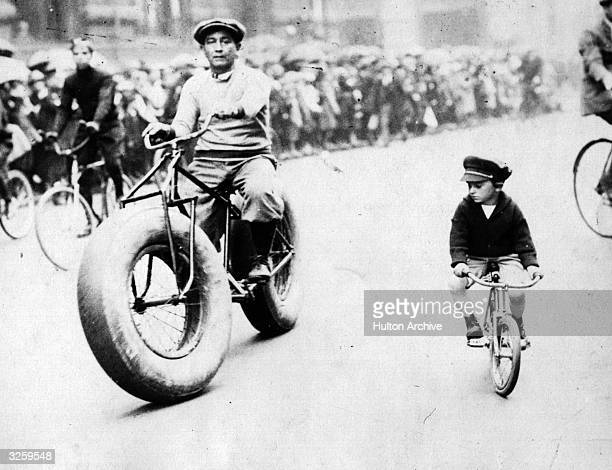 A bicycle equipped with baloon tyres and a 'baby' bike are side by side in the Safety Day parade in New York