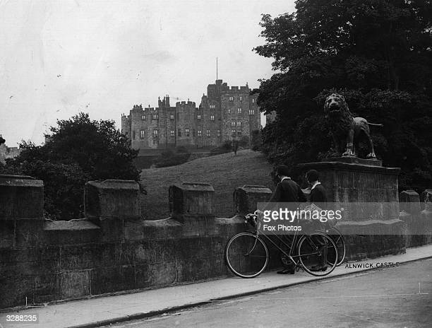 A couple of cyclist looking over a wall at Alnwick Castle