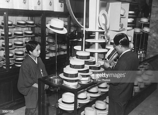 A customer buying a straw hat at a Japanese shop