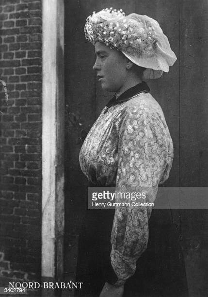 A Dutch girl wearing a patterened blouse and an elaborately decorated hat