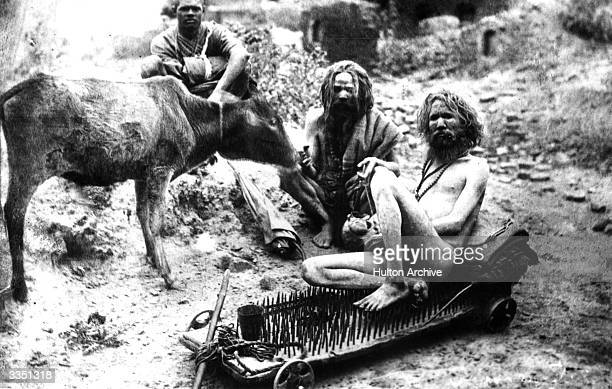 A fakir or sadhu sitting on a bed of nails which is on wheels