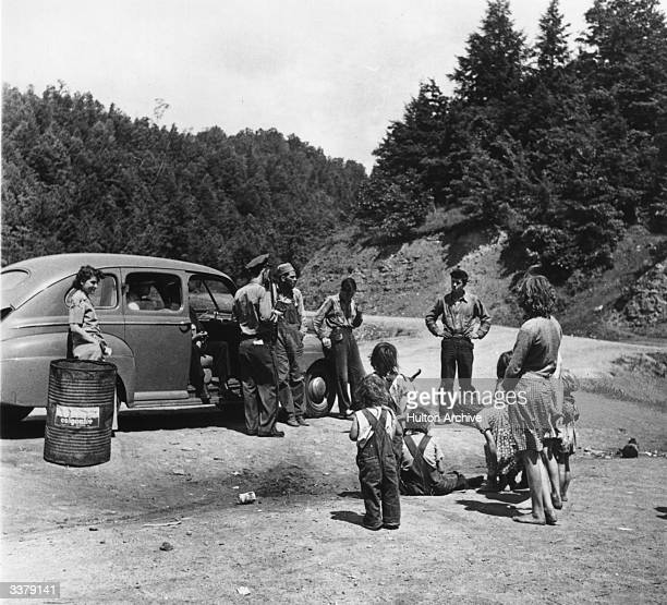 Group gathered round a car during the Great Depression in the USA.