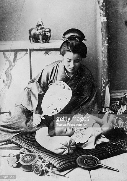 A Japanese mother fans her baby who is lying on a cushion on the floor The mother's hair is styled in a bun on top of her head held in place with...