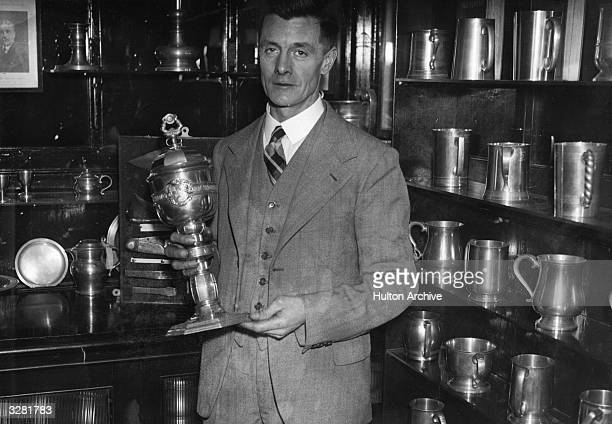 A man stands beside shelves of pewterware jugs and holds a pewter trophy