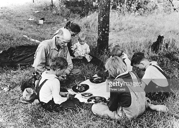 A migrant family saying Grace before their noonday meal by the side of the road East of Oklahoma