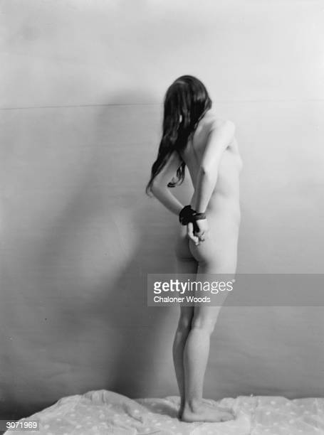 A photographer's model with her hands tied behind her back