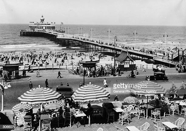 Pier at Scheveningen, a seaside resort in Holland. Striped umbrellas shade a beachside cafe in the forefront.