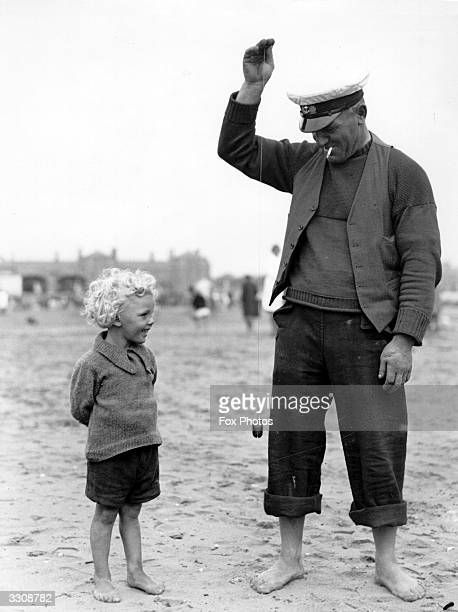 A small child watching a man playing with a yoyo on a beach
