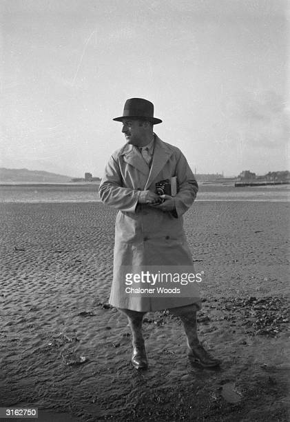 A solitary gentleman holding a camera occupies an isolated spot of the beach He wears a trilby plusfours and a rain coat