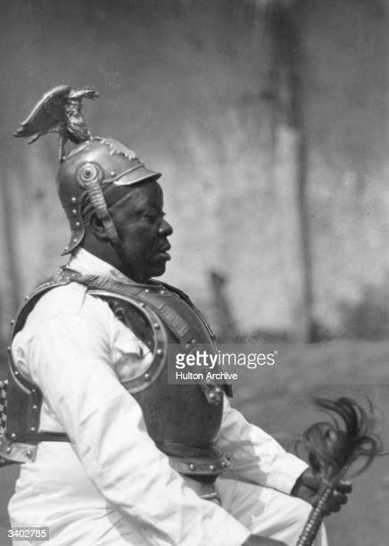 A tribal chief in Britishcontrolled Cameroon wears a German military headdress and breast plate during a native ceremony The uniform is a remnant of...