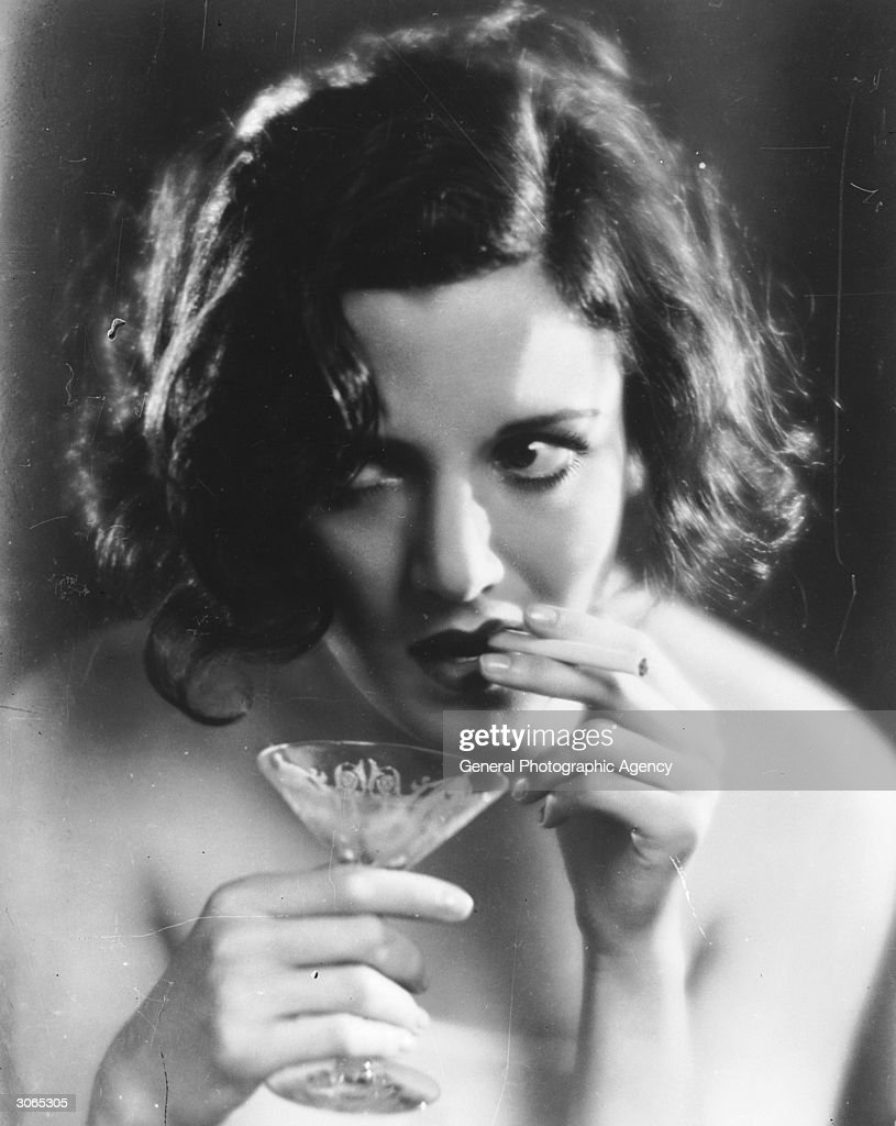 A woman smokes a cigarette while holding a cocktail glass in the other hand.