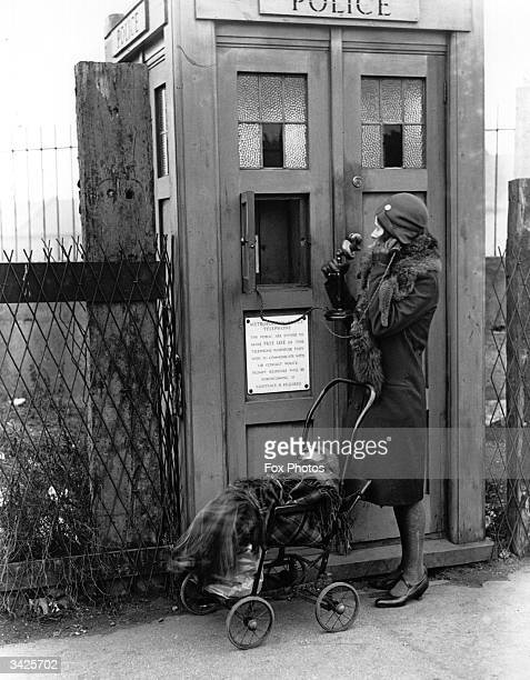 A woman uses an Emergency Police Call Box in London