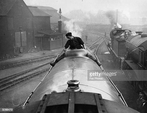 A worker sitting astride a locomotive whilst cleaning the boiler
