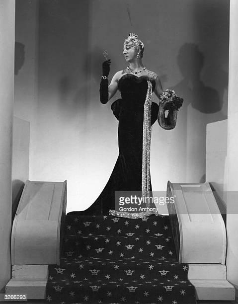 Actor Douglas Byng crossdressed as a rather elegant lady smokes a cigarette