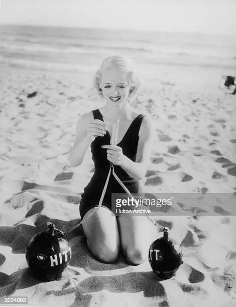 American actor Bette Davis kneeling on a beach in a swimsuit lighting a pair of bombs