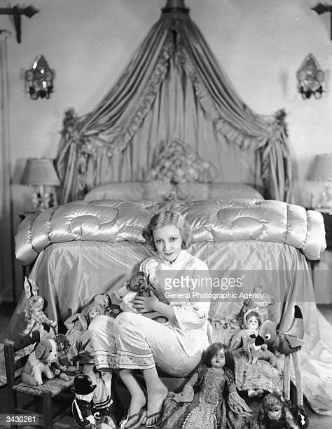 American actress Bessie Love born Juanita Horton surrounded by toys in a sumptuous bedroom