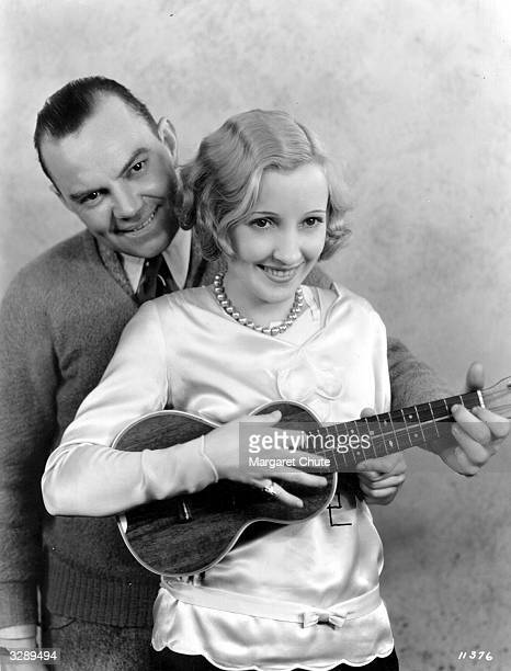 American actress Bessie Love tries her hand at the ukelele with the aid of entertainer Cliff Edwards known as Ukelele Ike