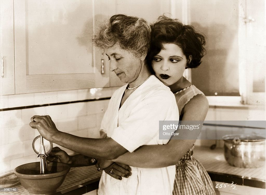 American actress Clara Bow, the 'It' girl, helps her housekeeper in the kitchen of her Beverly Hills home.