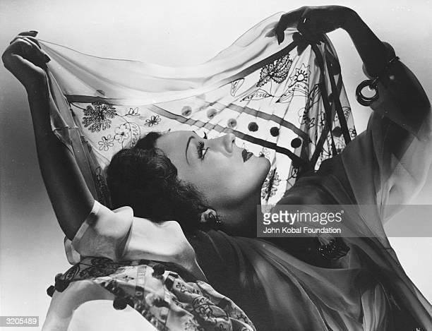 American actress Gloria Swanson holds a silk scarf up to the light framing her profile