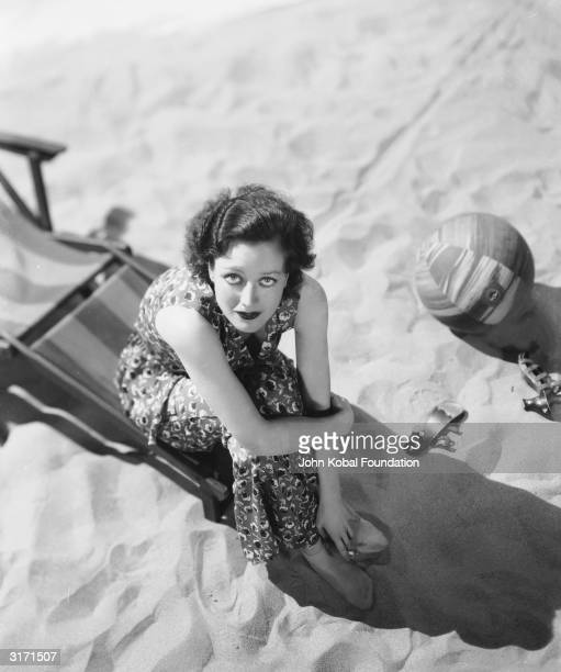 American actress Joan Crawford sitting on a deckchair on the beach