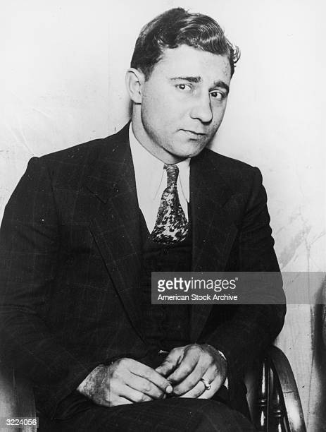 American criminal Jack 'Machine Gun' McGurn sitting in a chair in a suit and tie