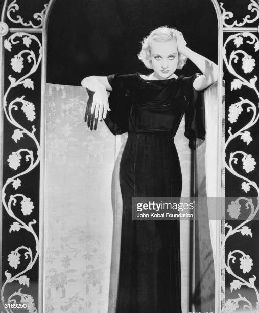 American film actress Carole Lombard wearing a fulllength black evening dress and a velvet cape