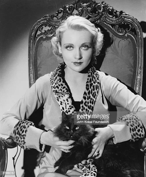 American film actress Carole Lombard wearing a jacket with a leopard skin collar and cuffs and holding a black cat on her lap
