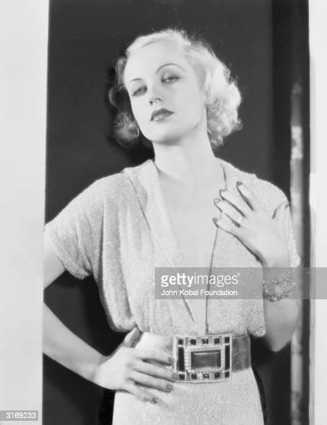 American film actress Carole Lombard wearing a large rectangular jewelled belt