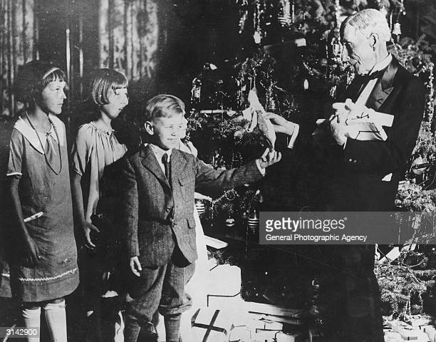 American oil magnate and philanthropist John Davidson Rockefeller handing out Christmas presents to a group of children