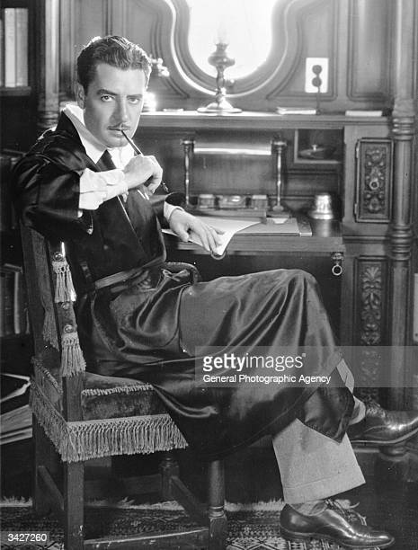 American silent star John Gilbert sucks thoughtfully on the end of a pen at his writing desk