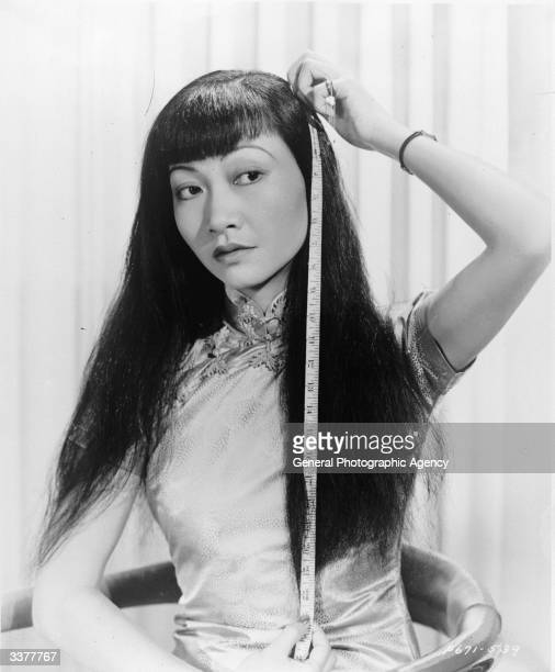 AmericanChinese actress Anna May Wong measuring the length of her hair