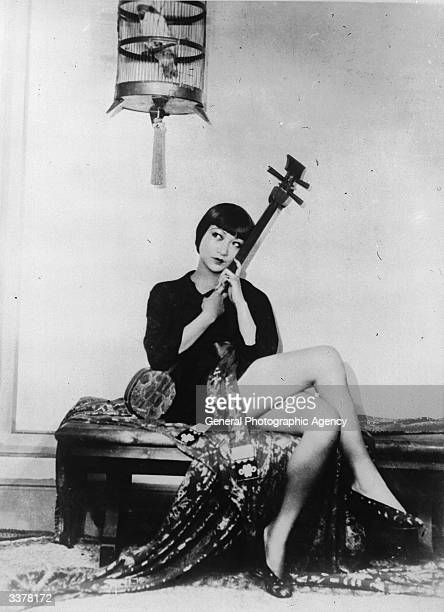 AmericanChinese actress Anna May Wong sitting holding a string instrument