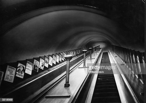 An escalator on London Underground with posters on show at the side