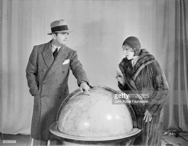 Canadian actress Mary Pickford and her husband, silent star Douglas Fairbanks point out locations on a globe.