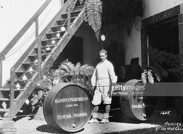 Casks containg madeira wine at a Blandy's a Funchal winery The worker is wearing unusual headgear with a sharp spike on the crown