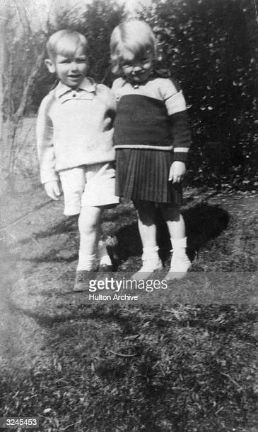 Childhood picture of American actor Marilyn Monroe at age four standing with a little boy outdoors