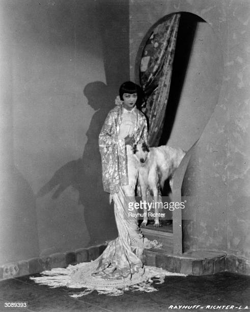 ChineseAmerican actress Anna May Wong wearing a flowing gown and standing next to a lean hound