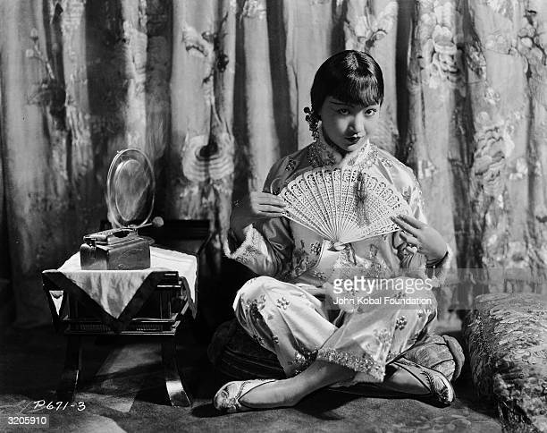 ChineseAmerican film star Anna May Wong sitting crosslegged